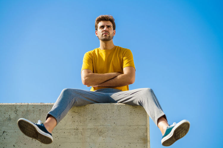 Low angle view of young man sitting against blue sky
