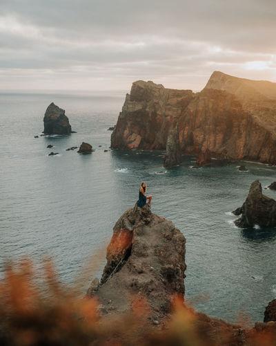 Womn sitting on rock by sea against sky