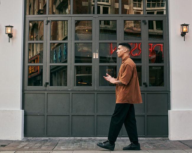 Full length of man standing against building