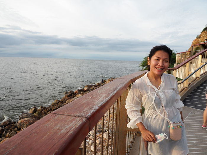 Portrait of smiling young woman standing by railing against sea