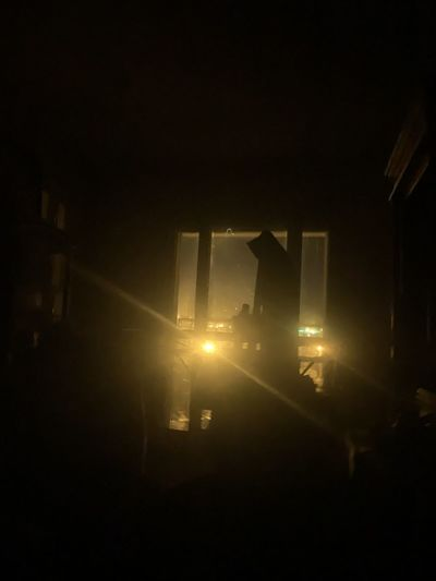Sunlight streaming through silhouette building at night