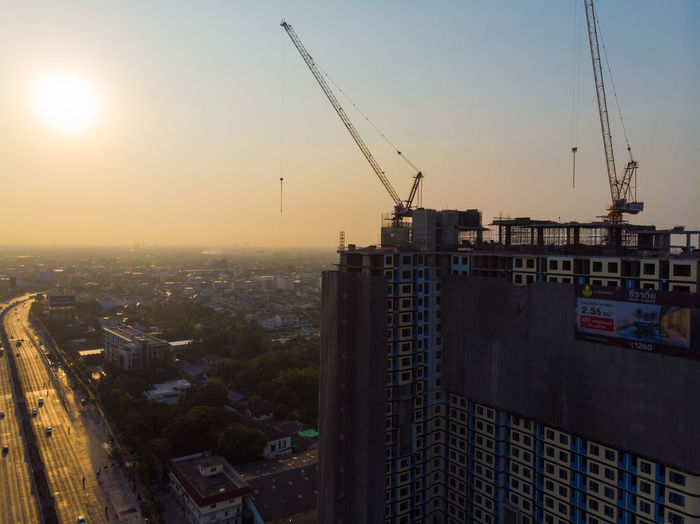 Construction site by buildings against sky during sunset