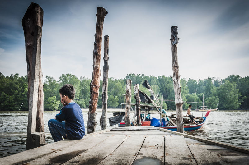 Boy Sitting On Jetty Clouds And Sky Fisherman Boat Getty Images Gettyimages Landscapes With WhiteWall Nature River View Seascapes Sitting Tranquility Tree Water Wooden Jetty Wooden Jetty Poles Wooden Pier Wooden Pier Pole Wooden Poles