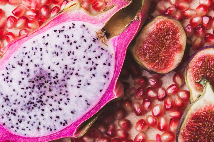 Close up sliced dragon fruit with figs, pomegranate seeds on the wooden background, top view. Flat lay. Pastel colors. Backgrounds Close-up Cross Section Day Food Food And Drink Freshness Fruit Full Frame Healthy Eating Indoors  No People Pink Color Pitaya Pomegranate Pomegranate Seed Seed SLICE