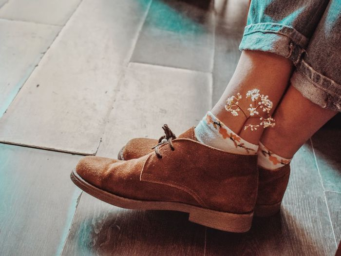 Low section of woman with flower in sock on hardwood floor