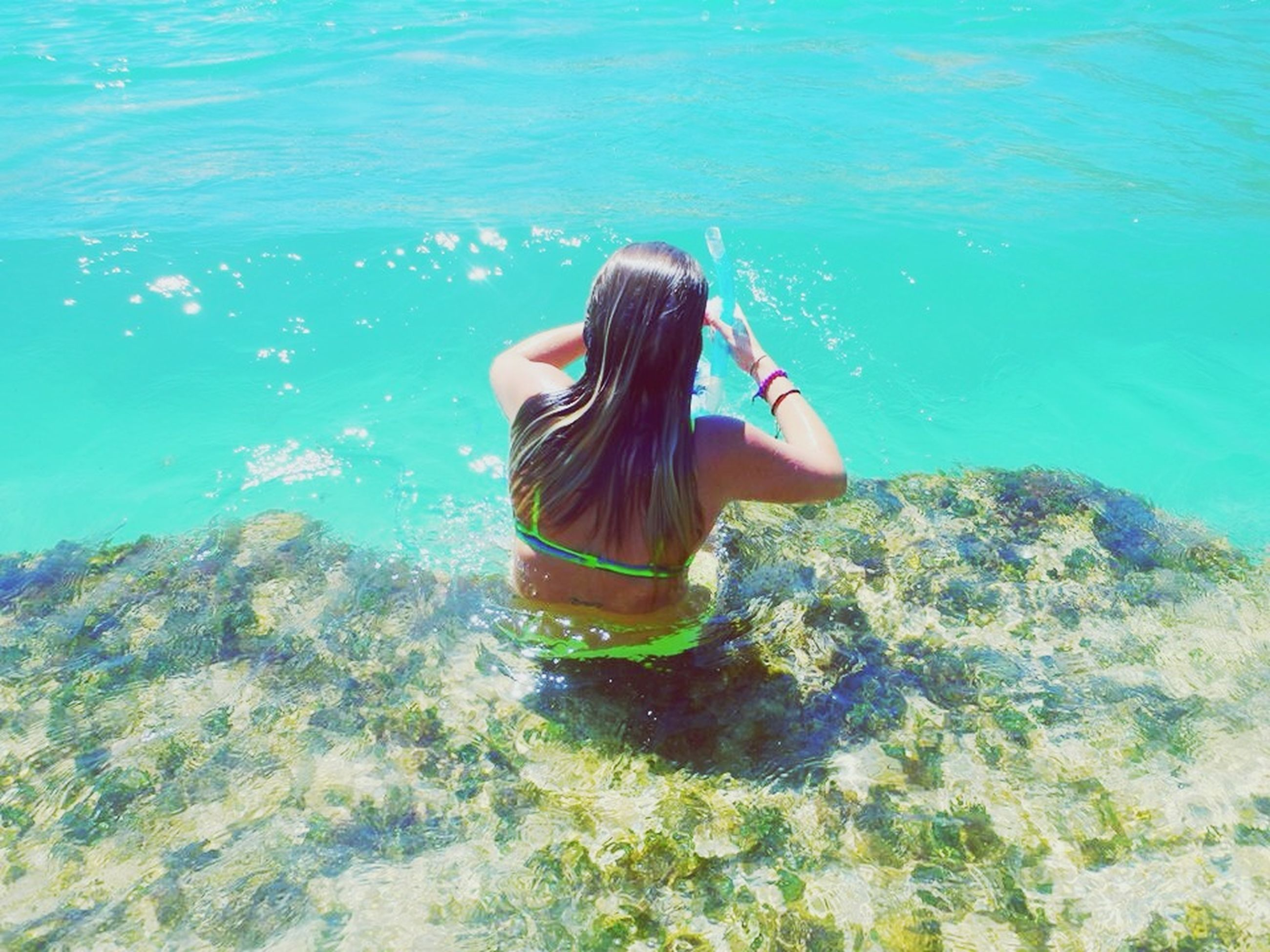 water, leisure activity, lifestyles, sea, blue, vacations, high angle view, full length, young adult, young women, relaxation, person, bikini, three quarter length, tranquility, nature, rear view, rock - object
