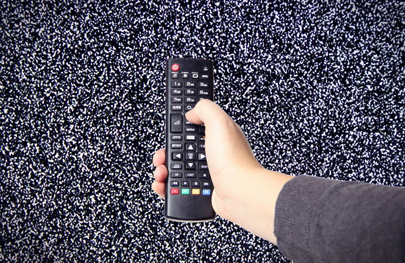 Close-Up Of Human Hand Holding Remote In Front Of Television