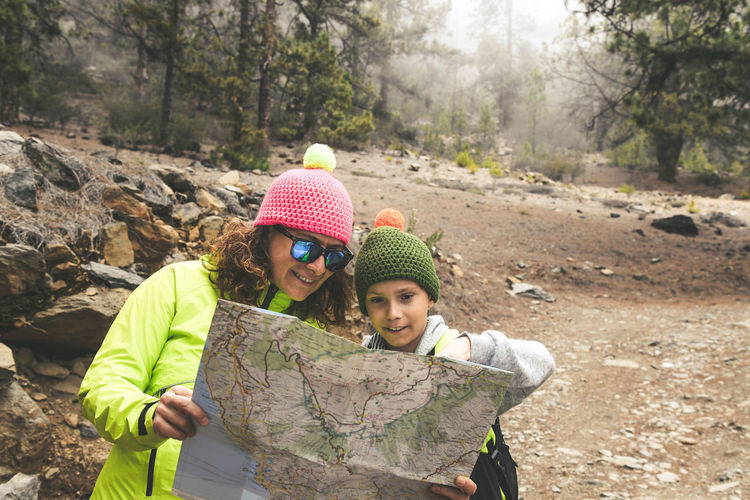 Mom and son together stop during a mountain forest trip. Couple look on the map the way to go. Mother teaches child how to navigate the journey. Positive concept of family and adventure togetherness. Two People Togetherness Women Clothing Knit Hat Hat Leisure Activity Child Males  Men Bonding Real People Childhood Females Adult Day People Lifestyles Nature Family Warm Clothing Positive Emotion Outdoors