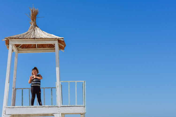 Girl standing in lifeguard hut while making heart shape gesture against sky