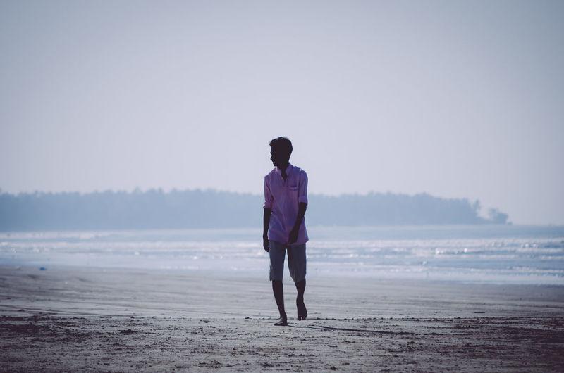 Full length portrait of man standing on shore against sky