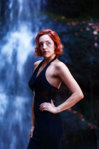 Woman standing against waterfall