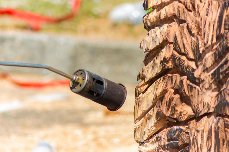 Close-up of blow torch by wooden sculpture
