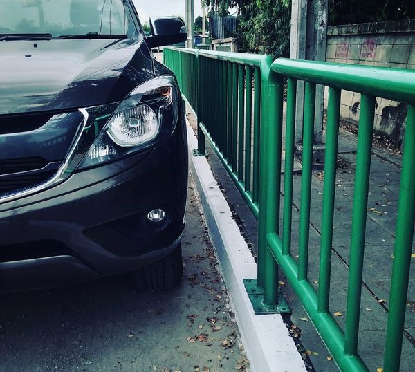 Close-up of car parked on road in city