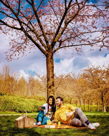 Couple Picnic Tree Young Women Happiness Smiling Women Sitting Full Length Sky Grass Growing Blooming Plant Life Self Portrait Photography Pixelated Pollen Selfie Artificial Intelligence Cursor Monopod Mother Board Rope Swing Photo Messaging Photographing Self Portrait In Bloom Flower Head Petal Fragility