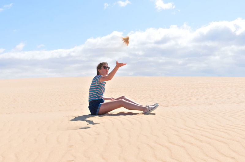 Full Length Side View Of Teenage Girl Throwing Sand While Sitting On Desert Against Sky During Sunny Day