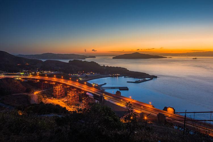 High angle view of illuminated sea against sky at dusk