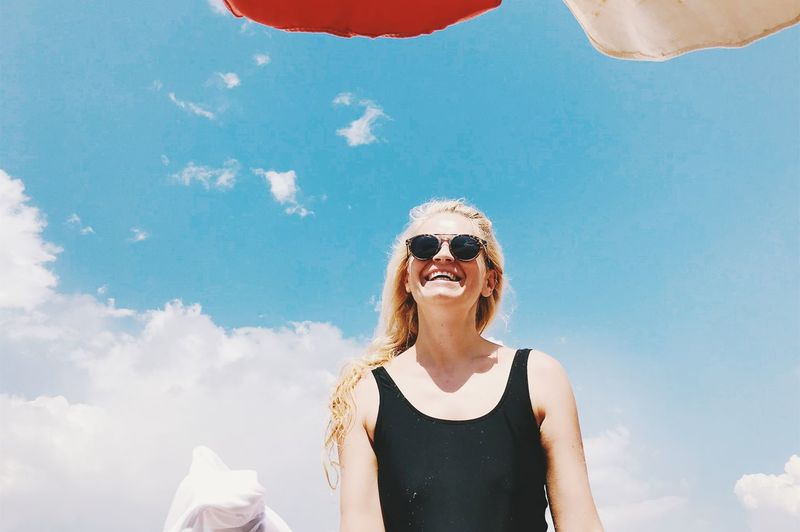 Low angle view of smiling woman wearing sunglasses against sky