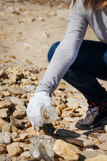 Low section of woman picking plastic bottle