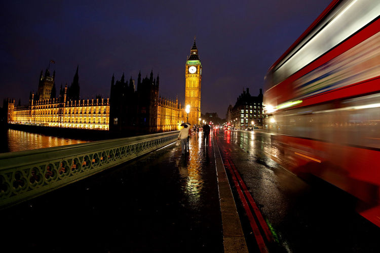 Red bus moving by big ben in city at night