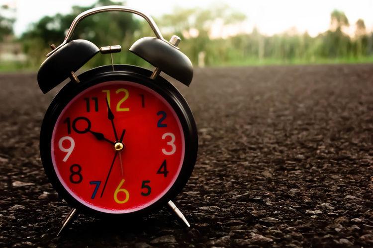 Close-Up Of Alarm Clock On Field