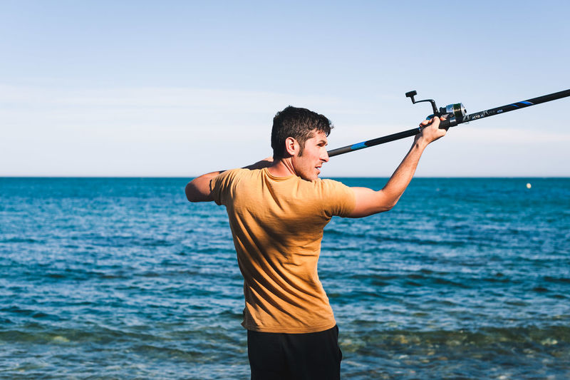 Beauty In Nature Casual Clothing Day Fishing Horizon Over Water Land Leisure Activity Lifestyles Males  Men Nature Non-urban Scene One Person Outdoors Real People Scenics - Nature Sea Sky Standing Three Quarter Length Water