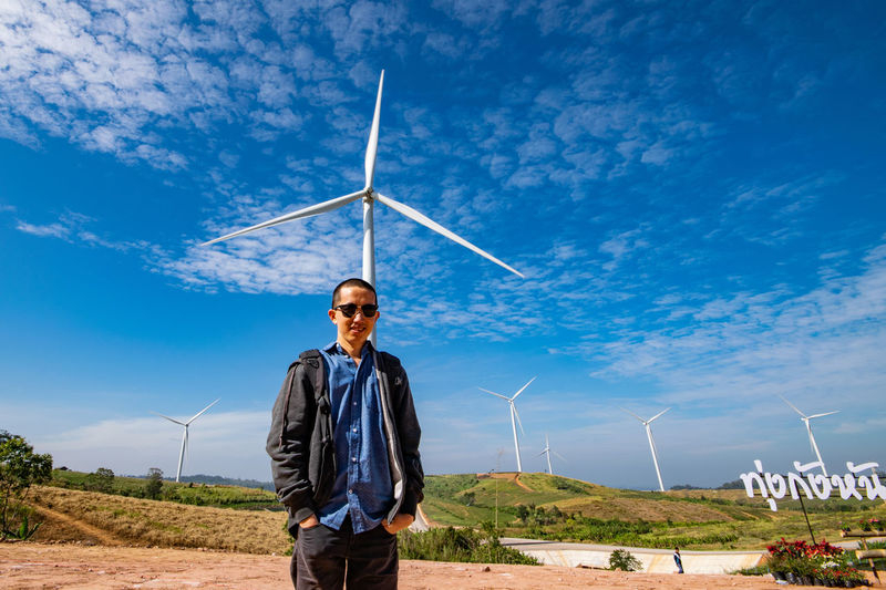Man standing on land against wind turbine and sky