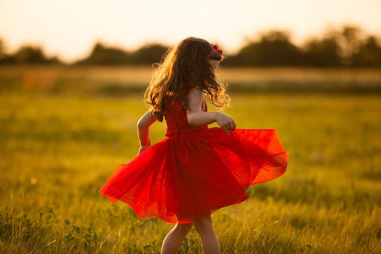 Girl walking on field against sky
