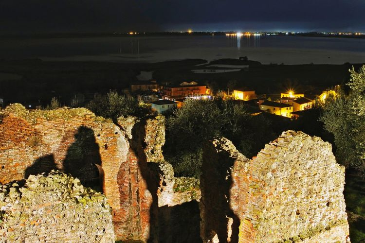 High angle view of illuminated rocks by sea against sky at night