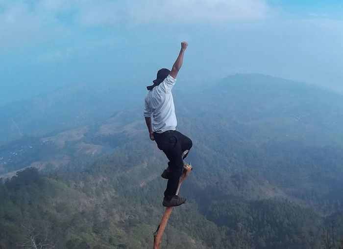 Full Length Of Man On Branch Over Mountain Against Sky