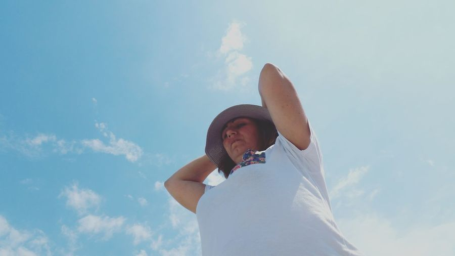 Low angle view of mature woman with arms raised standing against sky during sunny day