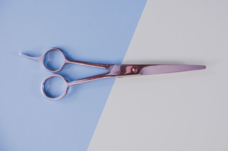 Directly Above Shot Of Scissors Over Colored Background