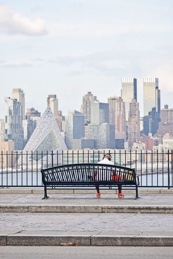 Rear View Of Man Sitting On Bench In City