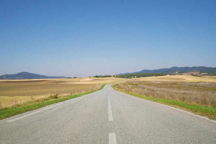 Road passing through landscape against clear sky