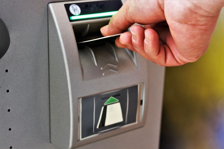 Close-up of hand withdrawing money at cashpoint
