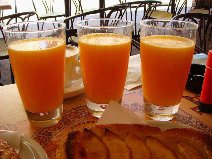 Three glasses with fresh orange juice on a table at an outdoor bar in summer. Concept of detox, healthy eating, summer Food And Drink Table Drink Food Glass Freshness Drinking Glass Healthy Eating Orange Color Still Life No People Close-up Breakfast Orange Fruit Juice Orange Juice  Meal Detox Summer Healthy Vitamin Diet Dieting Tropical Juice
