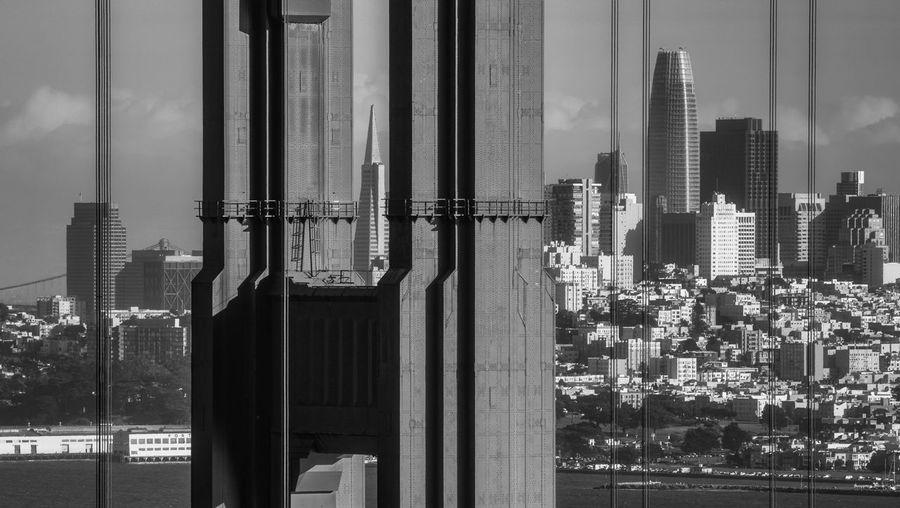 Modern buildings in city against sky behind golde gate bridge