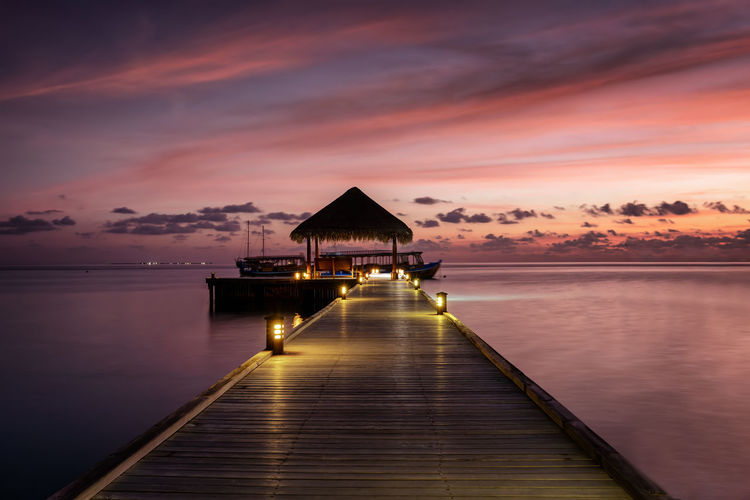 Wooden pier into the sunset with a water lodge at the Maldives islands Sunset Water Sky Cloud - Sky Sea Tranquility Beauty In Nature Tranquil Scene Scenics - Nature Architecture Orange Color Nature Pier Dusk Idyllic Reflection The Way Forward Built Structure No People Outdoors Horizon Over Water Pier Lodge Maldives Romantic Tropical Climate Tropical Paradise Paradise Wooden Sky And Clouds Evening Ocean