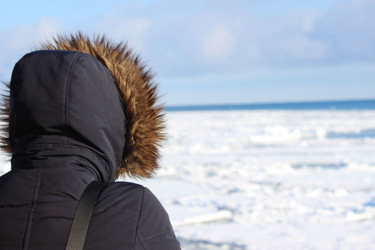 Rear view of woman wearing warm clothing standing on snow covered beach against sky