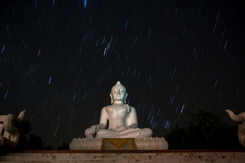 White Buda at night Sculpture Human Representation Art And Craft Representation Statue Low Angle View Spirituality No People Religion Night Male Likeness Belief Sky Nature Tree Creativity Architecture Star - Space Idol