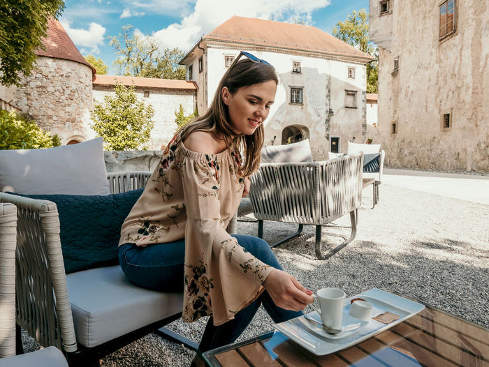 Portrait of happy young woman inside a castle courtyard. woman having a cup of coffee.