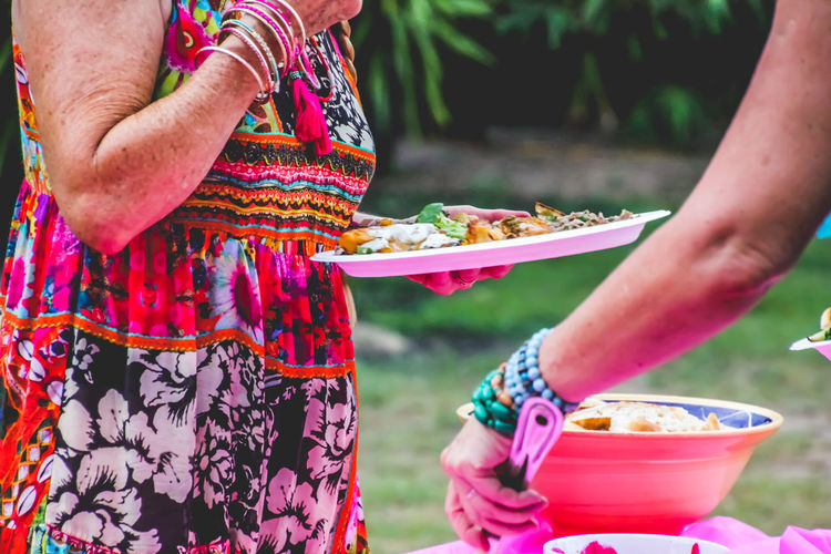 Midsection Of Two Women Eating Food Outdoors
