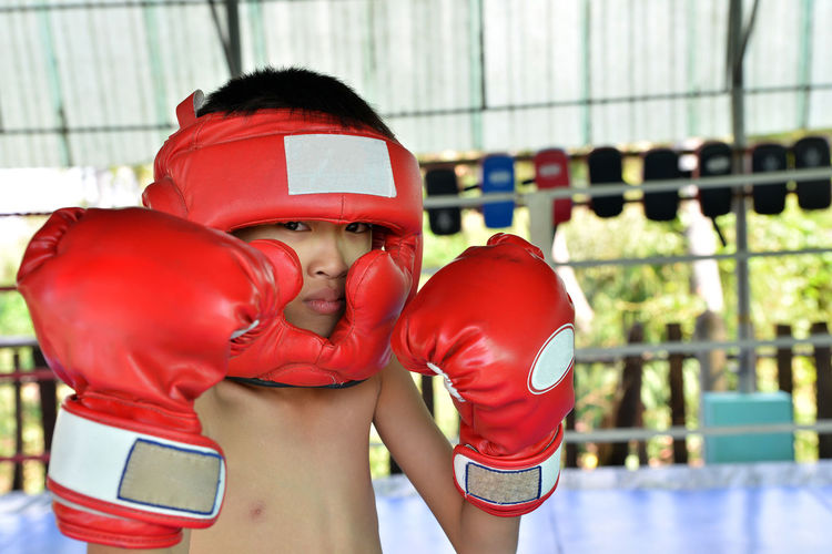 Portrait of shirtless boy in practicing boxing