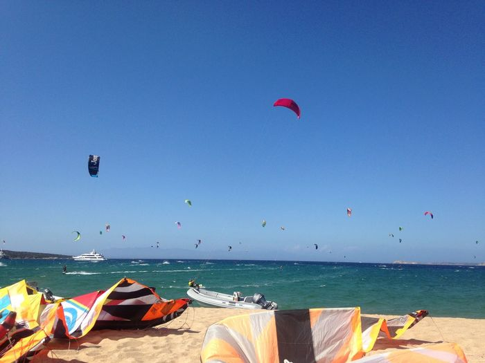 Water Sea Sky Beach Land Blue Nature Horizon Sunlight Beauty In Nature Sport Scenics - Nature Incidental People Clear Sky Paragliding Flying Horizon Over Water Tranquility Day Outdoors