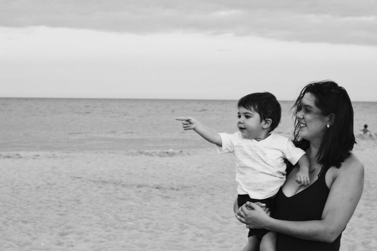 Happy mother carrying baby boy pointing against sky at beach