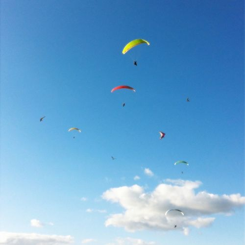Paragliders flying against sky