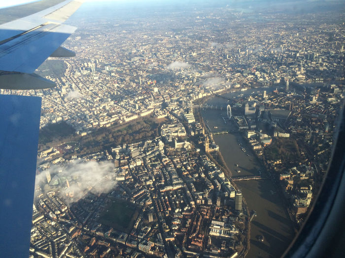 Aerial view of cityscape seen through airplane glass window