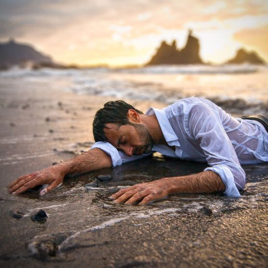 EXHAUSTED MAN ON BEACH AFTER SHIPWRECK