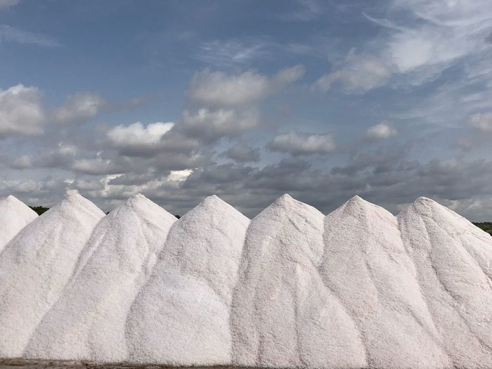 Low angle view of heap of salt against sky