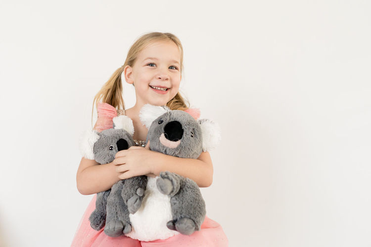 Portrait of smiling girl with toy against white background
