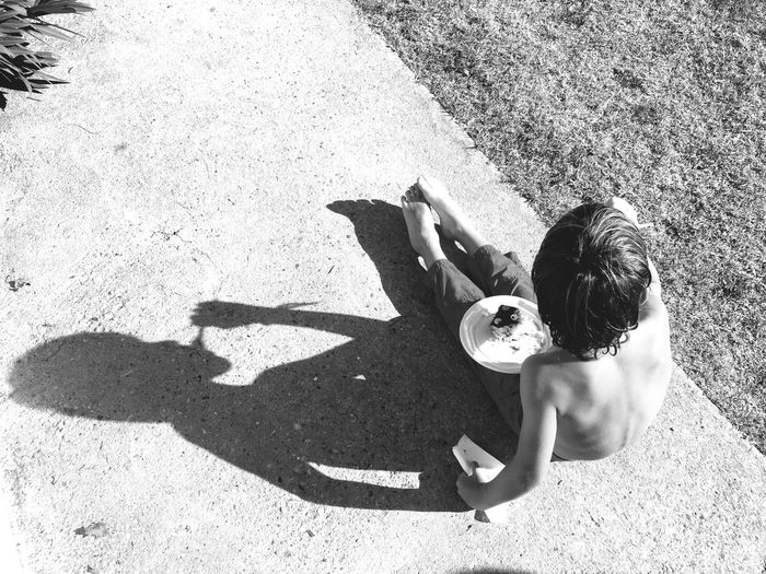 High Angle View Of Shirtless Boy Eating Cake While Sitting On Footpath By Field
